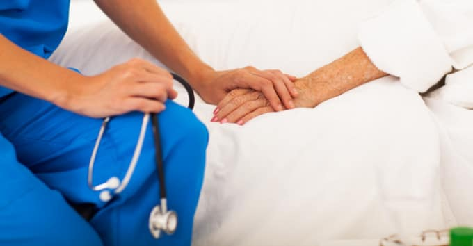 Nurse holding an old lady by the hand